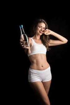 Modello di fitness femminile che tiene una bottiglia d'acqua
