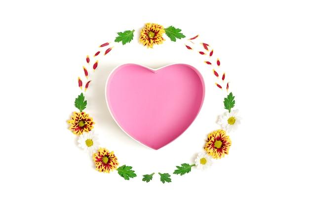 Modello di forma del contenitore di regalo di cuore, fiori gialli, rossi, aster bianchi, foglie verdi isolate su bianco