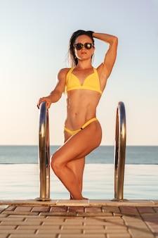 Modello di forma fisica della donna castana in bikini giallo che esce dallo stagno