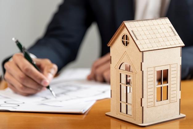 Modello di giocattolo in legno con persona che scrive in background