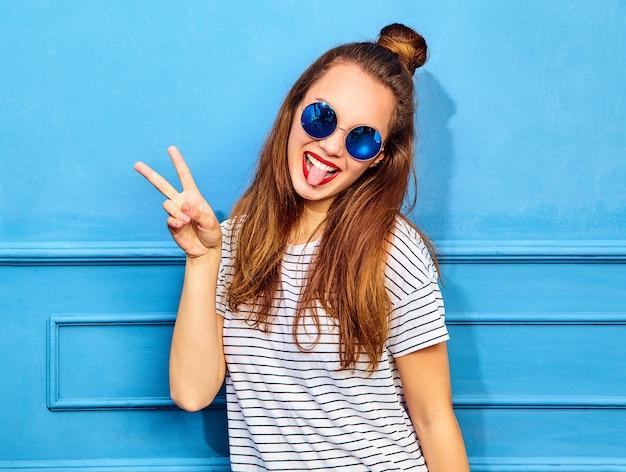 Modello di giovane donna alla moda in abiti casual estivi con labbra rosse, in posa vicino alla parete blu. mostra del segno di pace e della sua lingua
