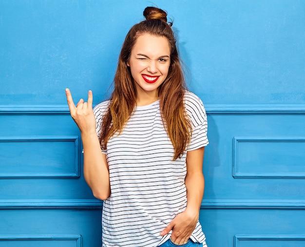 Modello di giovane donna alla moda in abiti casual estivi con labbra rosse, in posa vicino alla parete blu. sbattere le palpebre e mostrare il segno del rock and roll