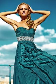 Modello di giovane donna bionda sexy in abito da sera in posa su sfondo blu cielo