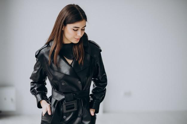 Modello di giovane donna che indossa un lungo cappotto di pelle nera