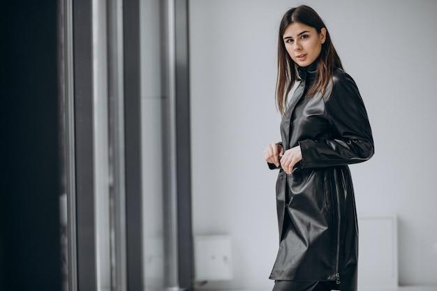 Modello di giovane donna che indossa un lungo cappotto di pelle