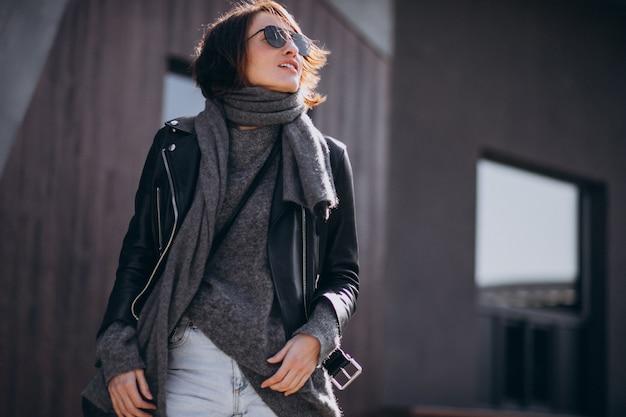 Modello di giovane donna in giacca di pelle fuori strada