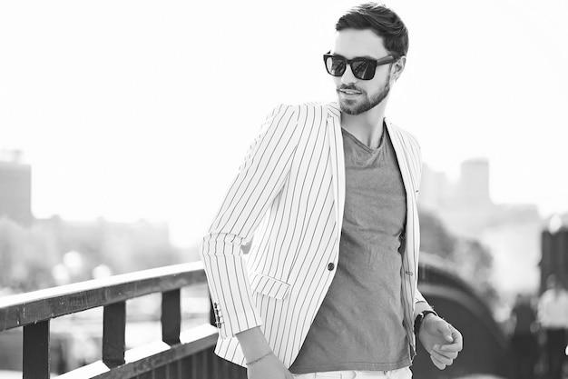 Modello di giovane uomo d'affari bello felice fiducioso alla moda nello stile di vita del panno dei pantaloni a vita bassa del vestito nella via