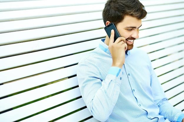 Modello di giovane uomo d'affari sorridente bello seduto sulla panchina del parco in panno casual hipster parlando sul telefono cellulare