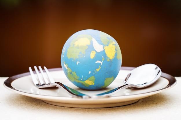 Modello di globo posizionato sul piatto con forchetta per servire menu in hotel famosi. cucina internazionale