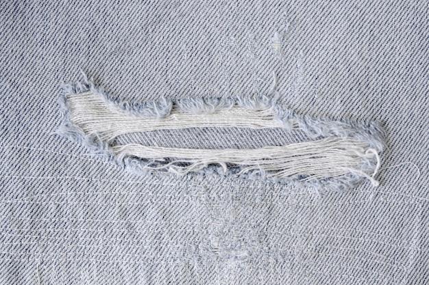 Modello di lacrima e vecchio sui pantaloni in denim, dettaglio jeans texture per lo sfondo.