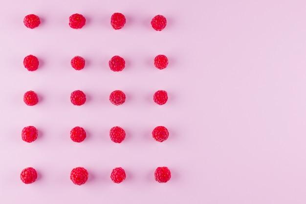 Modello di lamponi su sfondo rosa. dieta colorata e cibo sano. sfondo di lamponi. vista dall'alto. disteso. copyspace