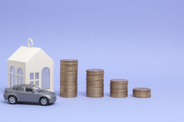 Modello di macchina grigia e casa con monete sotto forma di un istogramma su uno sfondo viola. concetto di prestito, risparmio, vendita, locazione di proprietà