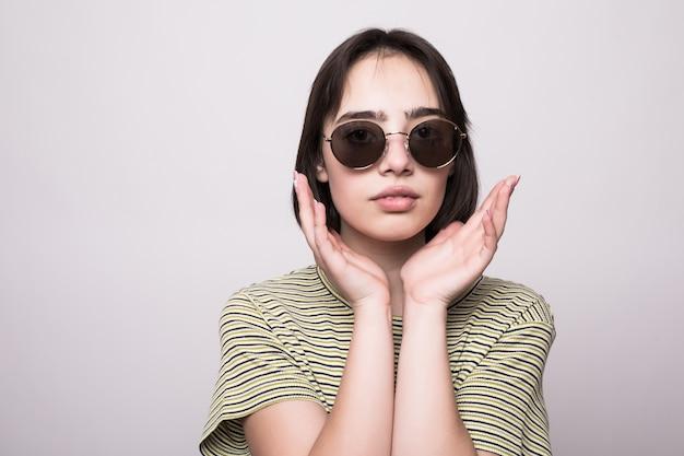 Modello di moda con i capelli corti. giovane ragazza in occhiali da sole con le mani vicino alla posa del viso