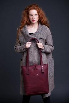 Modello di moda dei capelli rossi che tiene grande borsa di cuoio rosso scuro su fondo scuro. ragazza che indossa un maglione lungo.