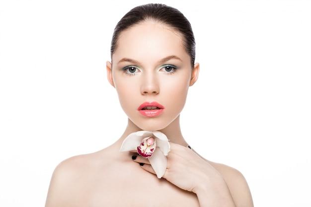 Modello di moda di bellezza che tiene orchidea bianca alla stazione termale