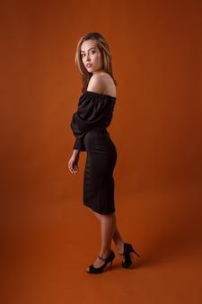 Modello di moda elegante in abito nero con profonda scollatura, scarpe tacco alto su arancione