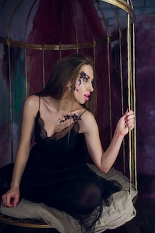 Modello di moda in abito fantasia in posa gabbia d'acciaio