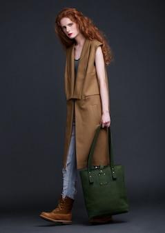 Modello di moda rosso dei capelli che tiene grande borsa di cuoio verde su fondo scuro. ragazza che indossa giacca senza maniche lunghe con jeans e stivali.