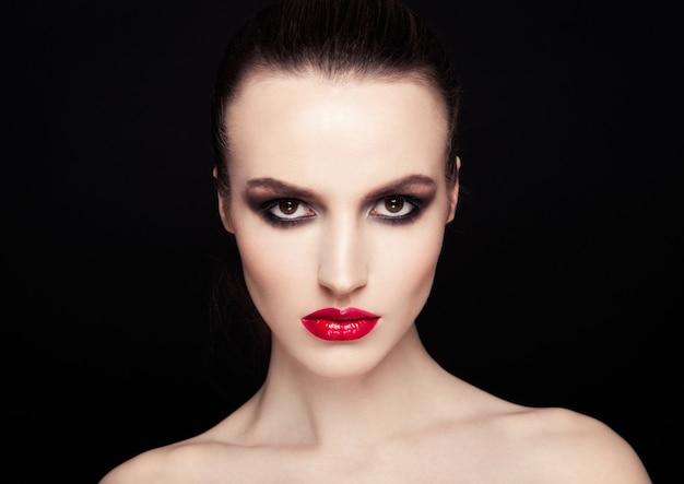 Modello di moda rosso di trucco delle labbra degli occhi affumicati di bellezza su fondo nero