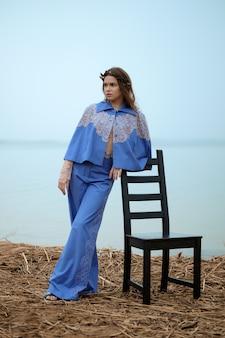 Modello di moda solo calmo che si siede sulla sedia in un giorno nuvoloso su una spiaggia.