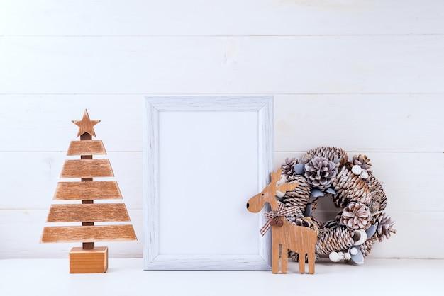 Modello di natale con cornice bianca, corona di coni, albero di legno e cervi su legno bianco