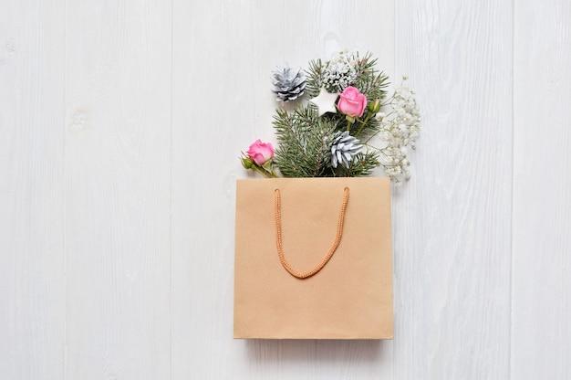 Modello di natale. pacchetto kraft con rami di abete decorati a natale