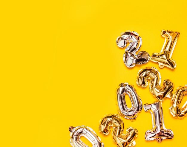 Modello di palloncini numero stagnola oro e argento su sfondo giallo.