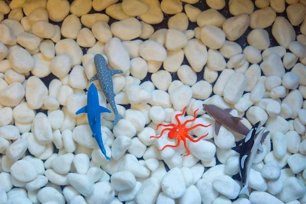 Modello di pesce artificiale o finto sulla pietra bianca.
