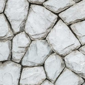 Modello di pietra di superficie del primo piano alla vecchia parete di pietra nei precedenti di struttura del giardino