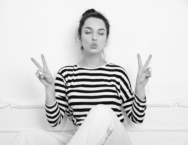 Modello di ragazza bella donna bruna con trucco nudo in abiti hipster estate in posa vicino al muro. seduto sul pavimento, dando un bacio e mostrando il segno della pace