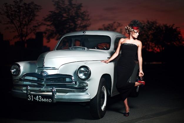 Modello di ragazza bionda bella moda sexy con trucco luminoso e acconciatura riccia in stile retrò, seduto nella vecchia auto