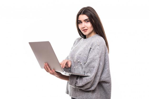 Modello di ragazza bruna in maglione grigio si siede sul pavimento e lavora studie sul suo laptop