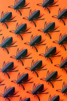 Modello di ragni di carta su uno sfondo arancione