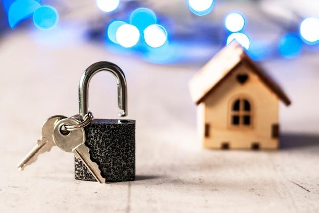 Modello di una casa di legno con una serratura e chiavi e bokeh