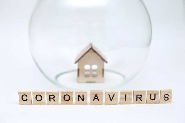 Modello di una casa in legno sotto una cupola di vetro e lettere in legno con la scritta coronavirus