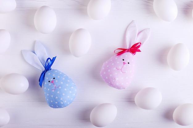 Modello di uova bianche, tra cui due coniglietti di pasqua fatti a mano