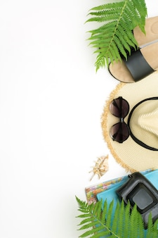 Modello di vacanza tropicale. sunhat della spiaggia della paglia, vetri di sole, schiaffi della spiaggia, foglia di felce su bianco.