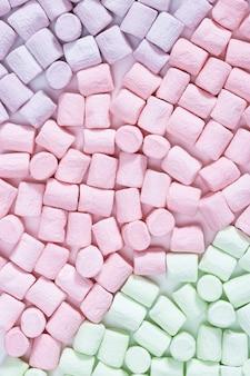 Modello dolce colorato marshmallow. il fondo dalle caramelle gommosa e molle luminose si chiude su. dessert color pastello. vista dall'alto.