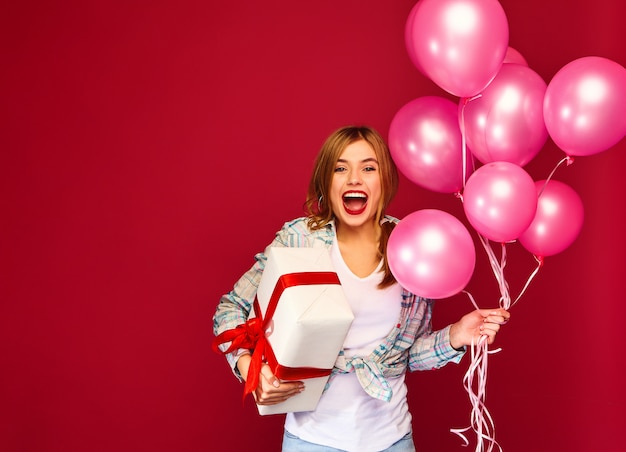Modello donna che celebra e che tiene scatola con regalo presente e mongolfiere rosa