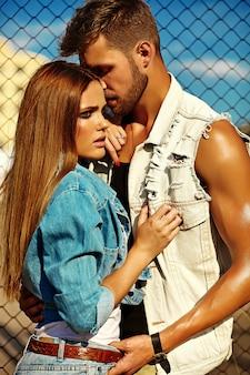 Modello donna con trucco luminoso e bell'uomo muscoloso in jeans dietro il cielo blu