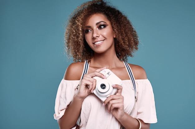 Modello elegante donna di colore con capelli ricci e macchina fotografica
