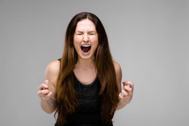 Modello emotivo plus size in piedi in studio con la bocca aperta che grida mostrando rabbia aggressiva vuole grattare