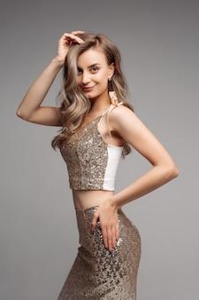 Modello esile in vestito beige sexy che guarda e che posa