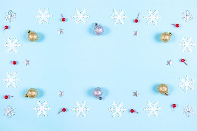 Modello fatto di decorazioni d'argento e dorate e fiocchi di neve su sfondo blu pastello.