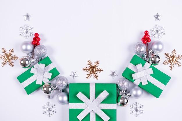 Modello fatto di scatole regalo, palline bianche e fiocchi di neve su sfondo bianco.