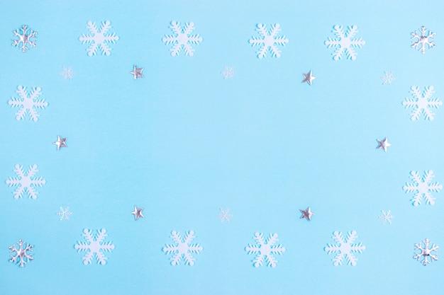Modello fatto di stelle d'argento e fiocchi di neve su sfondo blu pastello.