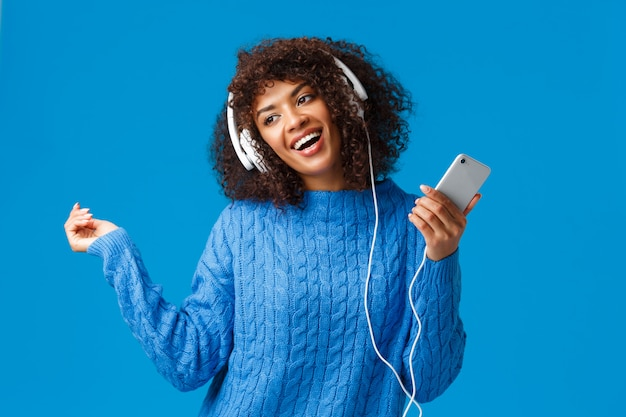 Modello femminile afroamericano adorabile allegro e spensierato in maglione di inverno
