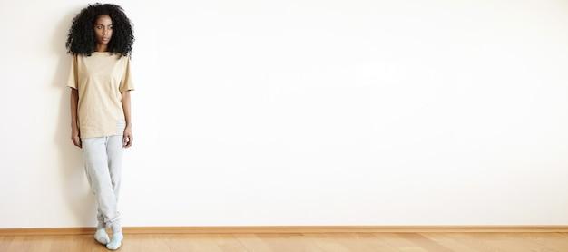 Modello femminile attraente alla moda dalla carnagione scura con l'acconciatura afro che guarda lontano mentre posa in interni al muro bianco, indossa abiti casual e tiene le gambe incrociate. scatto a figura intera, orizzontale