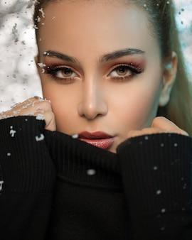 Modello femminile biondo con maglione nero