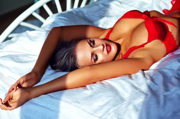 Modello femminile che indossa lingerie rossa sul letto la mattina